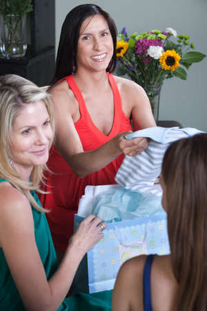 Smiling pregnant lady with friends holds baby clothes photo