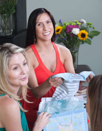 Smiling pregnant woman shows baby clothes to her friends  photo