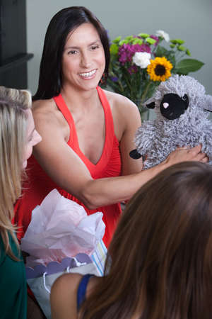 Expectant mom with friends holds baby shower gift