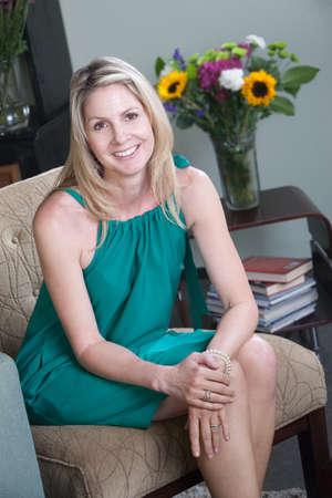 Happy middle-aged Caucasian woman relaxes on chair Stock Photo