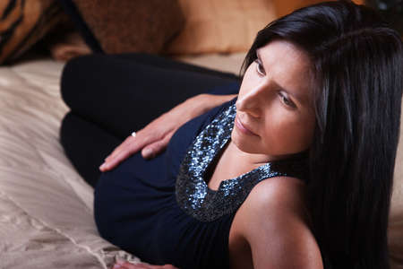 Beautiful young expectant mom relaxes on a bed  photo