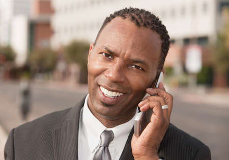 Confident African-American businessman smiles while on phone call photo