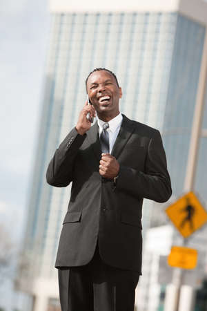 Excited African-American businessman in city on phone