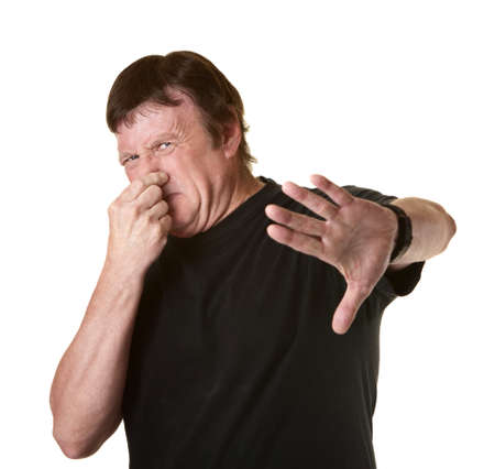 Mature Caucasian man on white background pinches his nose