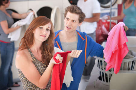 laundromat: Upset man and woman with stained clothes in laundromat