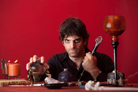 evil man: Evil man holds sceptre and crystal ball over red background