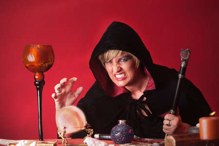 Scary witch with sceptre and crystal ball over red background photo