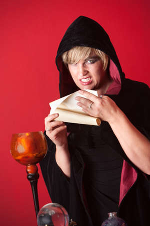 Evil witch reciting spells from a scroll photo