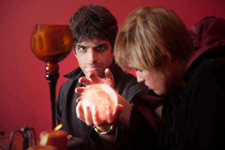 foretell: Occult couple hold crystal ball over red background