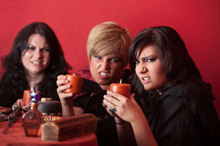 coven: Witch coven with candles over red background