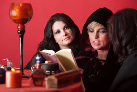 wicca: Witch recites spells from a book with two other women