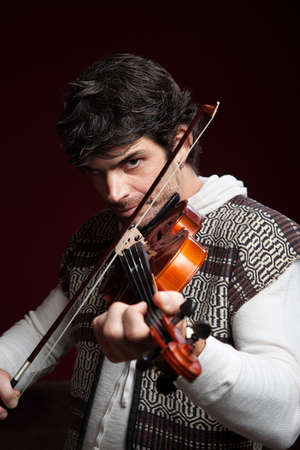 violins: Serious handsome Caucasian man plays violin Stock Photo