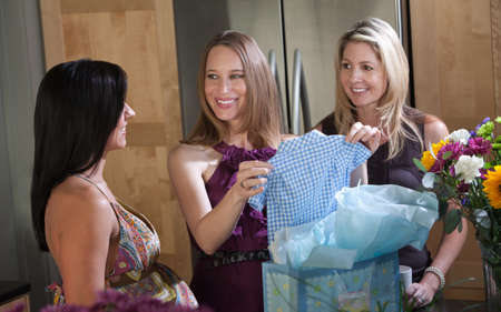 Pregnant lady holds blue baby clothes with friends in kitchen photo