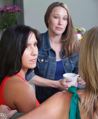 conversaciones: Mujer embarazada seria conversaciones con sus amigos Foto de archivo