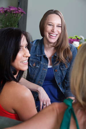 Beautiful young pregnant woman laughs with friends photo