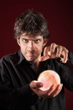 psychic: Caucasian fortuneteller holds glowing crystal ball