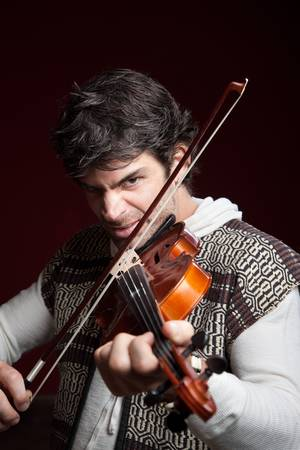 aggressively: Serious Caucasian man aggressively plays a violin