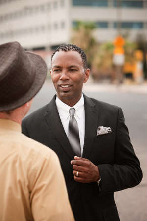 chats: Handsome African-American businessman chats with his friend  Stock Photo