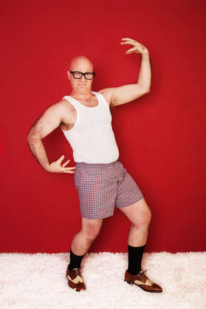 dweeb: Bald Caucasian man wearing boxer shorts shows of biceps over maroon background