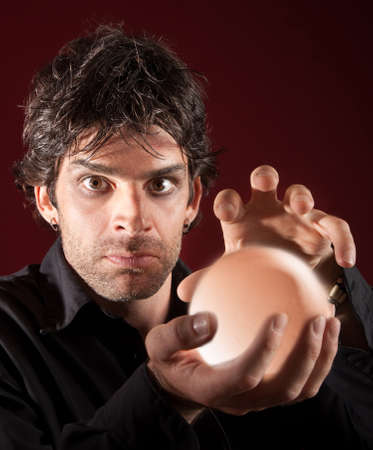 wicca: Serious fortune teller holds crystal ball over maroon background