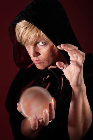 predict: Hooded blonde female fortuneteller with her crystal ball