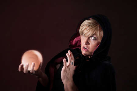 predict: Caucasian female fortuneteller wearing black viel holds crystal ball over maroon background