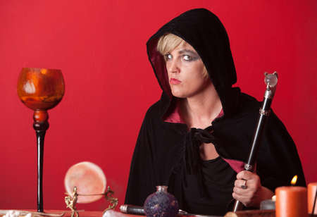 sceptre: Caucasian witch holds sceptre over red background