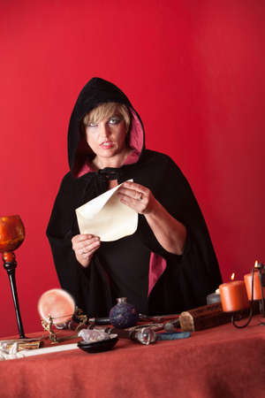 Hooded witch reads a spell over red background photo