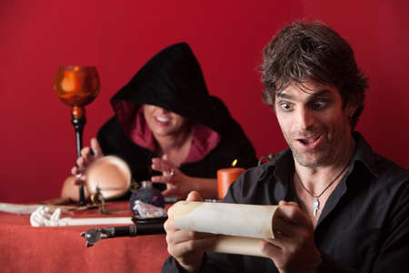 psychic: Man with scroll smiles with hooded fortuneteller in background
