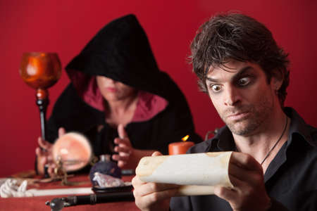 Surprised man reads his future with fortuneteller in background photo