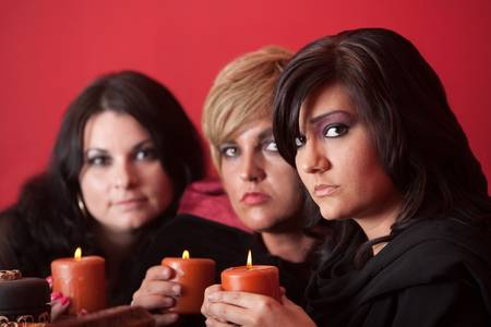 wicca: Three witches hold candles over red background