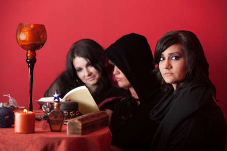 Witch wearing black veil reads spells with partners over maroon background photo