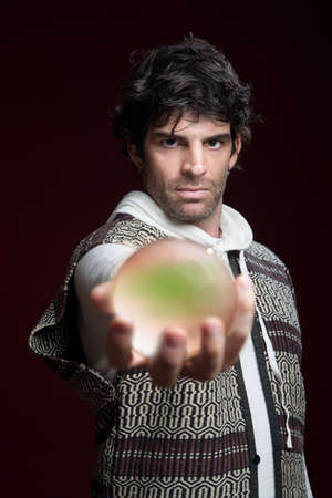 predict: Caucasian male fortuneteller holds glowing crystal ball