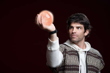 predict: Caucasian man holds up a crystal ball  Stock Photo