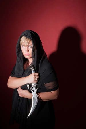 cloak and dagger: Caucasian witch wearing in hood with athame dagger