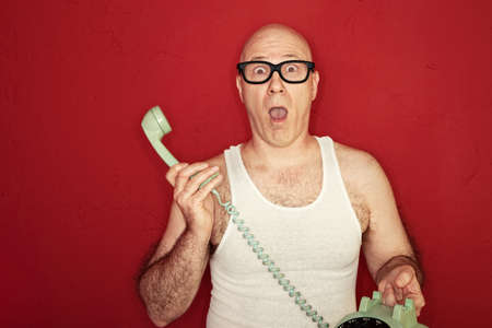 gasp: Shocked bald Caucasian man holds telephone over maroon background