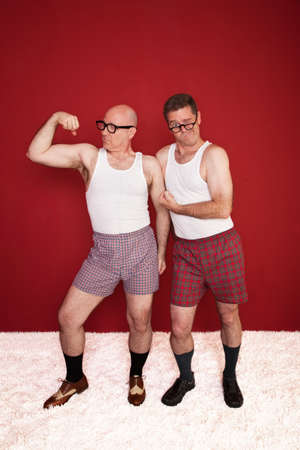 Two middle-aged men in boxers flex their muscles photo