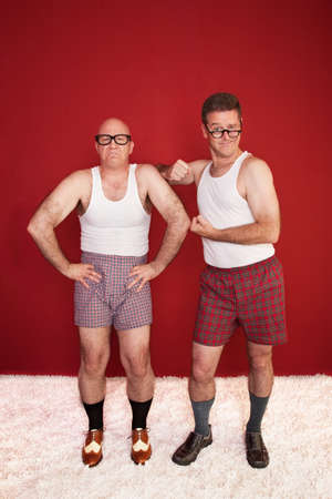 Two Caucasian men wearing boxer shorts show off biceps over maroon background photo
