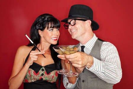 Happy Caucasian couple enjoy martini and cigarette over maroon background Stock Photo - 10553283