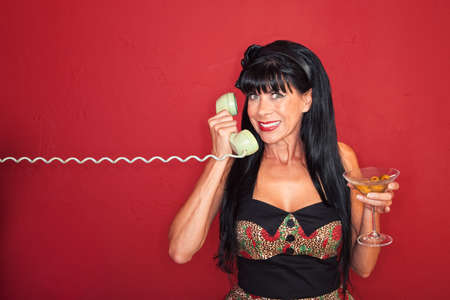 Smiling middle-aged woman on phone with a martini photo