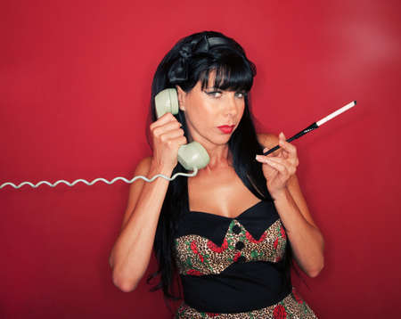 Retro-styled smoking woman on phone over maroon background photo