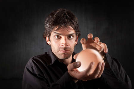 Serious fortune teller holds crystal ball over maroon background photo