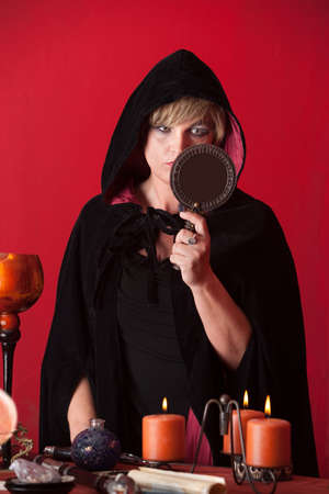 wicca: Caucasian witch looks into a mirror over red background Stock Photo