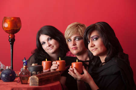 wicca: Three smiling witches hold candles over red background