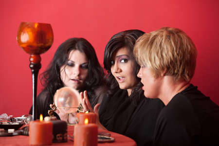wicca: Three women fortunetellers gaze at a crystal ball Stock Photo