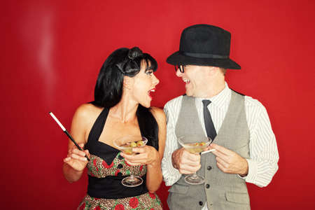 Excited Caucasian couple enjoy martini and cigarette over maroon background Stock Photo - 10553326