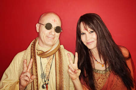 Smiling guru with woman gestures peace sign over maroon background photo