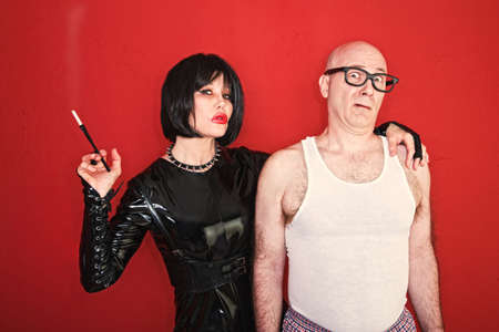Dominatrix woman wraps her arm around fearful client.