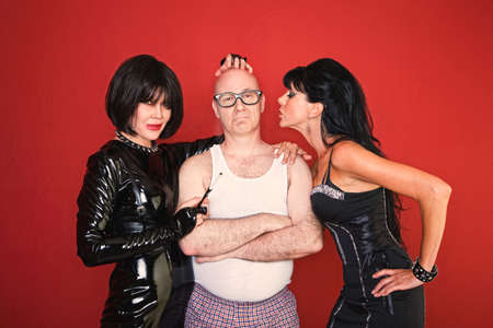 beautiful bdsm: A confident man is surrounded by two playful dominatrix women. Stock Photo