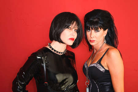 Two dominatrix women stare straight down the camera. photo